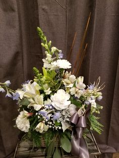 Blue bayou is a new fall arrangement made in muted shades of blue and grey. Faux blue/grey pumpkins are added to white and blue flowers. Designed in a grey wooden cube with hanging cedar and greens it also has cattails and a pewter satin ribbon. This is a lovely change from the traditional fall centerpiece. #bluethanksgiving #bluebayou #greypumpkins #rusticthanksgiving #countrytables #novemberflowers #mesaflowers #mesaflowershop #lovinglyflowers