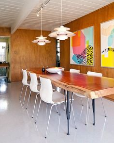 Large colorful art punctuate this dining space in a contemporary take on mid-century modern design.