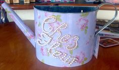 Cheap watering can, added crystal to spout, painted the name of the house with gold, after drying, glued pearls on top. Im going to put silk flowers in and keep it out of the weather.