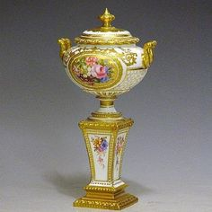 Royal Crown Derby Bulbous Lidded Urn Shaped Vase on pedestal in ivory the oval gilded reserves painted with Summer flowers by Gregory with similar floral sprays to pedestal sides, signed, having matt gilded scroll handles, finials and rims, 9in, stamped (restoration)