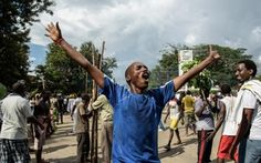 A Burundian man rejoices over the announcement of coup d'etat on President Nkurunziza, raising hands to the sky eyes closed, mouth agape, while another watches and smiles.