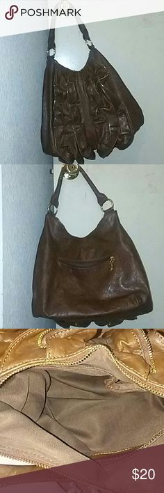 Cute brown shoulder bag with ruffle zipper design Cute brown shoulder bag with ruffle design and gold zipper embellishment.  Very roomie.  Has a zipper compartment in the back, it's a pretty decent size.  Can probably fit a paperback pocket novel in her, stephen king's it size.  Inside: on one side there are two open pockets, one big rectangular pocket, big enough to fit my android with extra room.  The other open pocket is a smaller.  Probably more ideal for like your pen, lipstick, change…