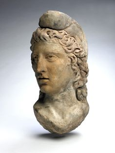 Life-size head of Mithras wearing a Phrygian cap and long curls. This stone statue fragment was found in London in 1954 buried in an underground chamber devoted to the secret cult of the bull-slayer god, popular among soldiers in the Romans Legions. 2nd-3rd C.