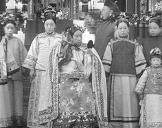 The Cixi Empress Dowager Cixi 慈禧太后 with attendants in front of Paiyunmen, Summer Palace, Beijing, 1903. Cixi was an enthusiastic advocate of theater arts. She commissioned new libretti and updates of traditional dramas, and she organized a personal acting troupe composed of court eunuchs. In this group photograph, Cixi assumes a theatrical pose.