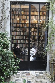 Love the high double doors and patio courtyard outside and the huge shelf of books!