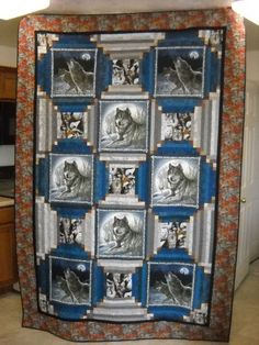 Quilter said: Made from pillow panels surrounded by log-cabin strips with cornerstones. I bought the pillow panels and the wolf print in the alternate blocks, but everything else was from stash. I did not remember buying the wolf print I used for the border, but there it was!