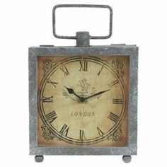 "Showcasing a metal frame and Roman numerals, this distressed pocket watch-inspired table clock brings antiqued appeal to your desk or mantel.  Product: ClockConstruction Material: Glass and metal Color: Brown and gray  Accommodates: Batteries - not included  Dimensions: 10.5"" H x 7.2"" W x 2.5"" D"