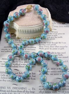 For your consideration is this lovely vintage cloisonne bead necklace. The beads are 12mm in size, and each are hand knotted on a light blue thread. The colors are vibrant, the stringing is good, and with the exception of a tiny (3mm) shallow chipping of enamel on one of the beads, in very good condition.