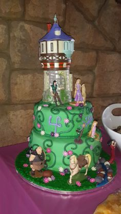 Rapunzel Birthday Cake - This cake was ordered for a 4 year old birthday party.  Two  tiers.  The top tier was, 8-inch/20Cm, hot pink vanilla cake with purple vanilla butter cream.  The bottom tier was 11-inch/28Cm, 2 layer cake, chocolate with raspberry jam and cocoa filling.  It was covered in green fondant, piped butter cream vines, and decorated with sugar flowers and Disney's Rapunzel action figures.
