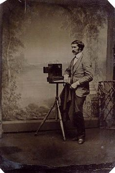 ca. 1860-90, [tintype portrait of a gentleman with his camera, standing before a painted backdrop]  via Artfact, Swann Auction Galleries