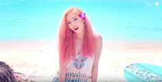 Girls Generation Party Music Video fashion - Band member with pink hair wears a fringe crop top in pink, hoop earrings, denim shorts, a belt, and a flower in her hair