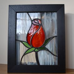 Stained glass rosebud set in a deep box frame. The frame makes it stable for display on shelves, tables or window ledges. £80 framed and £65 unframed from Radiance Stained Glass.
