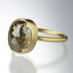 An 18k yellow gold ring with a 1.5mm, full round band and an oval smoky yellow rose cut diamond = 5.7 ct. Stone measures approximately 12mm x 10mm x 7mm. Size 6.75.