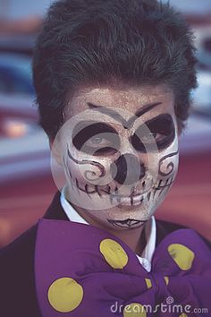 Boy dressed as Joker in  sugar skull day of the dead makeup for Halloween.