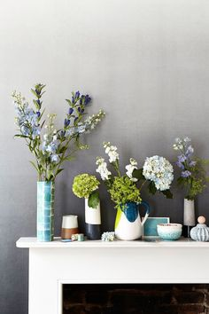 Display blooms in glaze-dipped ceramics against a faded wallpaper. Photography: Mark Scott