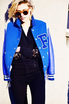 Sofie Valkiers of Fashionata wears a bold blue varsity jacket as a fashion statement paired with orange sunglasses
