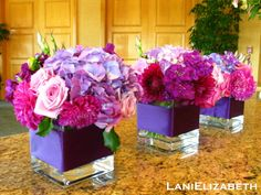 Great purple centerpiece - Clear cube vase wrapped in purple satin ribbon and filled with stock, dahlias, roses and hydrangea in shades of purple and fuchsia by Lani Elizabeth