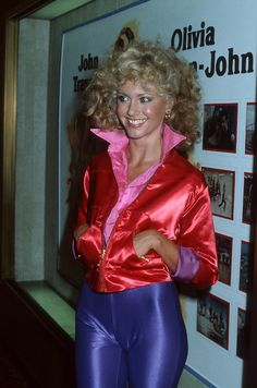 "Large crystal clear scan of multi-platinum singer Olivia Newton-John in a bright red satin jacket and tight blue disco pants - during a promotion for ""Grease"" at notorious disco Studio 54 in the summer of Olivia Newton John Grease, Olivia Newton John Physical, Disco Hose, Disco Pants, Studio 54, New York City, 1970 Style, Eartha Kitt, John Travolta"