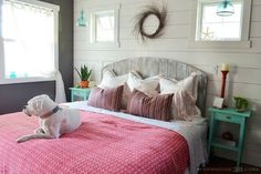 Love this cozy cottage bedroom with rustic barn wood headboard and planked walls eclecticallyvintage.com