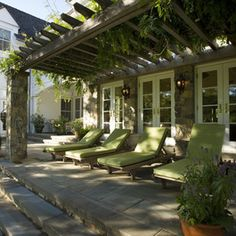 Pergola, covered in green vines. Green cushions. Soothing.