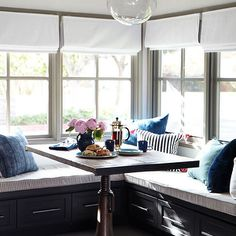 Eric Olsen Design - dining rooms - rustic wood beams, dining room wood beams, globe light pendant, reclaimed wood dining table, square dining table, salvaged wood dining table, industrial base table, industrial dining table, black banquette, built in banquette, black built in banquette, L shaped banquette, white roman shades, vaulted ceiling, eat-in kitchen, kitchen banquette, dining banquette, blue pillows, gray moldings, gray window moldings,