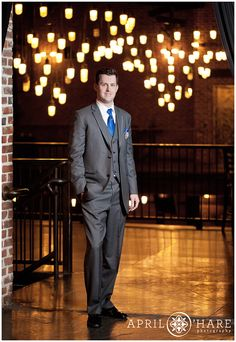 A professional portrait of the groom posing in front of the bright lights of the chandeliers at Mile High Station in Denver Colorado.  #DenverWedding #MileHighStation #ColoradoWedding #WinterWedding #Chandelier