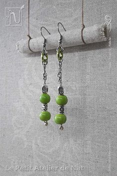 Réalisation [ Fait-Main ] avec du fil aluminium (Ø2mm), deux perles de verre coloré et des perles tibétaines, ainsi qu'une perle de rocaille et un anneau d'aluminium. Les crochets d'oreilles sont en acier inoxydable ainsi que la chaîne. Petites boucles d'oreilles ou boucles d'oreille à assortir avec tenue et maquillage, selon l'envie. Facile à mettre et enlever, la boucle d'oreille est légère et se dandine au gré des mouvements, avec de petits tintements agréables qui permettent de…