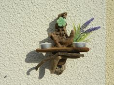 Driftwood Candle Holder Sconce made with beach combed driftwood and decorated with a green flower adornment and artificial lavender for a simplistic peice of driftwood in your home. Designed for one or two tea lighter candles. Candles can set the mood in your house, they help you relax and are great for romantic occasions, and you can hang these candle holders on any wall to give a warm glow; great for the Bedroom, Living Room or Bathroom.