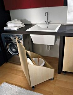 This DIY pallet wood storage bin with wheels provides movable storage under the sink.