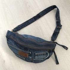 Repurposed Kuyichi denim crossbody bag with one main compartment, a front pocket and a back pocket with zipper Lined with black cotton I'm not good at bullshitting, you know that by now. Imagine the stuff you can put in it and where you can go with it :)) This one is a middle sized