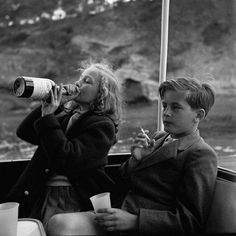 Yvonne Sayn-Wittgenstein-Sayn takes a swig from a bottle of champagne and Prince Alexander with a cigarette, 1955