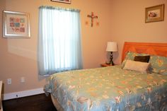 Bedroom with queen bed and ceiling fan.  For more details, visit our Facebook page at https://www.facebook.com/barefootescapebeachrental/