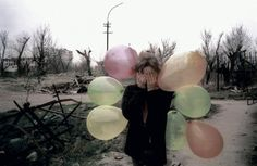 Girl with balloons. Destruction in the city center. Nothing has been rebuilt since the two wars. Grozny, Chechnya, Russia. March, 2002. © Thomas Dworzak / Magnum Photos