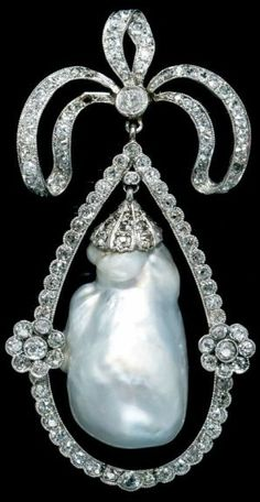 An Edwardian Platinum, Natural Baroque Pearl and Diamond Brooch, in a bow motif, containing one natural hollow pearl and numerous old mine and rose cut diamonds. #Edwardian #BaroquePearl #brooch