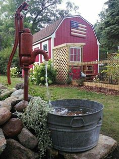 Red water pump in front of big red Barn.