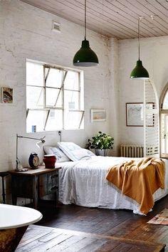 #Dormitorio con mucho factory feeling en el que la altura de la habitación, la madera envejecida tanto de suelo como de techo, las lamparas colgantes, la crudeza de la pared, los #muebles y la ventana de cuadrículas comoponen un espacio elegante a la vez que aspero.