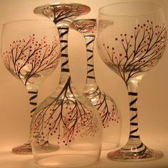 Set of four hand painted wine glasses. Red berries adorn the branches. The design wraps downward around the stem and fans out onto the base. The