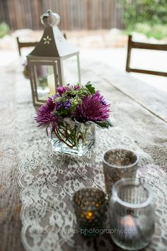 Smaller arrangements added with additional touches such as Lanterns or Votive Candles as a centerpiece is a simple way to save on cost!  #Centerpiece #BurlapAndLace #RusticWedding #OutdoorWedding #GrueneEstates #CountryWedding #LavenderWedding #WeddingFlowers #Lanterns #VotiveCandles  Lavender Spider Mums. Purple Statice. Queen Anne's Lace. Seeded Eucalyptus. Dusty Miller.  Danielle Williams Wedding. Photography via Michelle Jones Photography. Oakleaf Florist.
