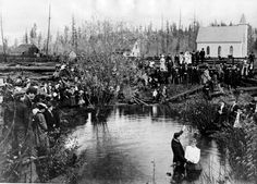 When this picture was taken in 1907, just after the Baptist Church was built in Battle Ground, regular procedure was holding of baptismal rites in a creek behind the church. Members of the congregation gather around as the Rev. Jones, church pastor, enters the water with a worthy candidate. The church can be seen in the background.