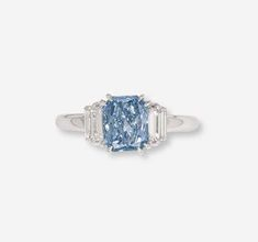 A COLOURED DIAMOND AND DIAMOND RING    Set with a cut-cornered rectangular-cut fancy vivid blue diamond weighing 1.01 carats flanked on either side by baguette-cut diamonds, mounted in platinum