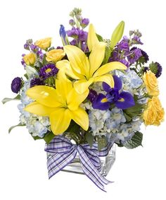 Touched by Sunshine-What a gorgeous color combination in this contemporary bouquet. Flowers include blue hydrangea, iris, yellow lilies, spray roses, stock and matsumoto asters. The flowers are arranged in a clear glass rectangular vase and tied with a coordinating bow. This special delivery will make someone as happy as a sunny Spring day. #ZeidlersFlowers #EvansvilleFlowers #GetWellFlowers