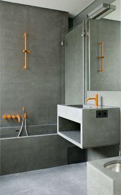 béton ciré salle de bain : baignoire encastrée; lavabo au design minimaliste et accents orange