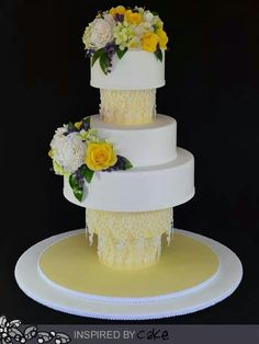 Very unique wedding cake with  pale yellow accents and white and yellow roses.  Click to enlarge the photo and you'll see what appears to be sugared lace hanging from the tiers.  Very pretty.  ᘡղbᘠ