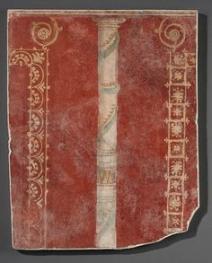 A ROMAN WALL PAINTING FRAGMENT  circa 1st century a.d.  Painted on a red ground, preserving a column at the center in white, with turquoise and yellow garlands spiralling along its length, with foliate borders in yellow on either side 28 in. (71.1 cm) high
