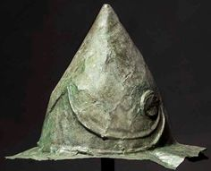 Hybrid Boeotian-Pilos helmet, hellenistic period, 2nd - early 1st century B.C. The skull of the helmet, measuring circa 22 cm with a hammered brow element rising to a point in the centre front, with volutes on either side. There is a famous depiction of this helmet type on the Domitius Ahenobarbus relief (late 2nd - 1st century BC) which was discovered in Rome and sparked debate on deployment in the Late Republican Roman Army. Private collection, from Hermann Historica auction