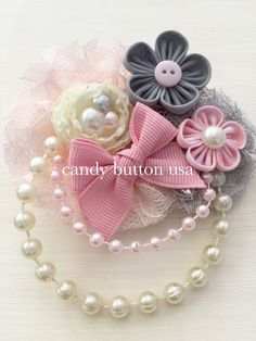Dress your little princess with this beautiful hairclip designed and handmade by CandyButtonUSA!!    This hairclip is adorned with different sizes handsewn fabric flowers, strains of synthetic pearls, and resin button. The whole piece measures approximately 4 long and 3 wide.  This item come attached to hairclip / brooch combo unless another type of clip or headband plastic/elastic is requested. Hairclip measure approximately 1 1/2 long. If you prefer another color please message me, Ill…