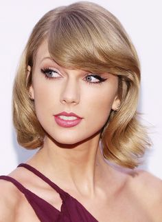 Taylor Swift stays true to her cat-eye and red lip combo, adding a festive touch with shimmery eyeshadow