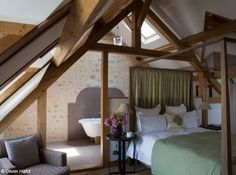 , la soupente de cette chambre accueille un lit à baldaquin qui sert de séparation avec la salle de bains.