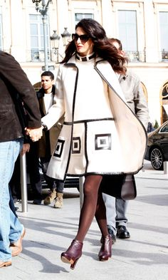 Très chic! The mom-to-be channeled her inner Parisian while in the City of Lights wearing an ivory shift dress and matching coat sold by William Vintage that featured chocolate brown vinyl trim and patch pockets.