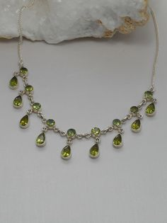 """Eighteen faceted dangling Peridot gemstones, bezel-set in 925-hallmarked sterling silver on a delicate chain. Length: 16-17""""+ Lobster claw clasp. Largest center vertical dimension: .75"""""""